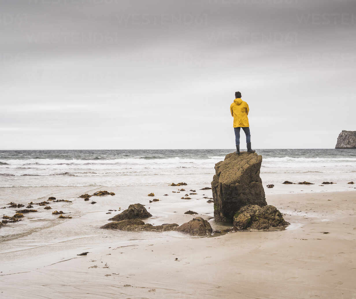 Young man wearing yellow rain jacket at the beach and standing on rock, Bretagne, France - UUF19680 - Uwe Umstätter/Westend61