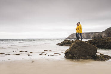 Young woman wearing yellow rain jackets and standing on rock at the beach, Bretagne, France - UUF19683