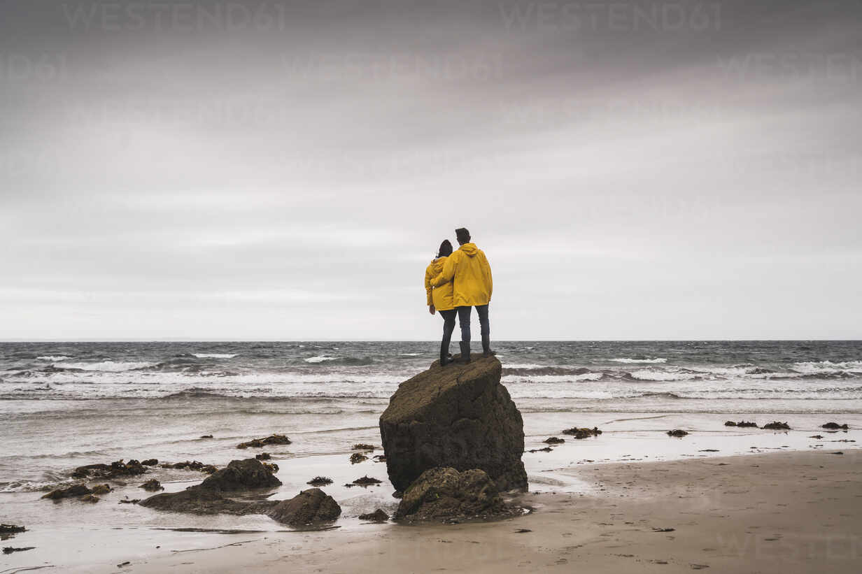 Young woman wearing yellow rain jackets and standing on rock at the beach, Bretagne, France - UUF19686 - Uwe Umstätter/Westend61
