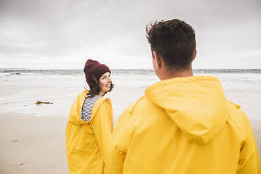Young woman wearing yellow rain jackets and walking along the beach, Bretagne, France - UUF19689