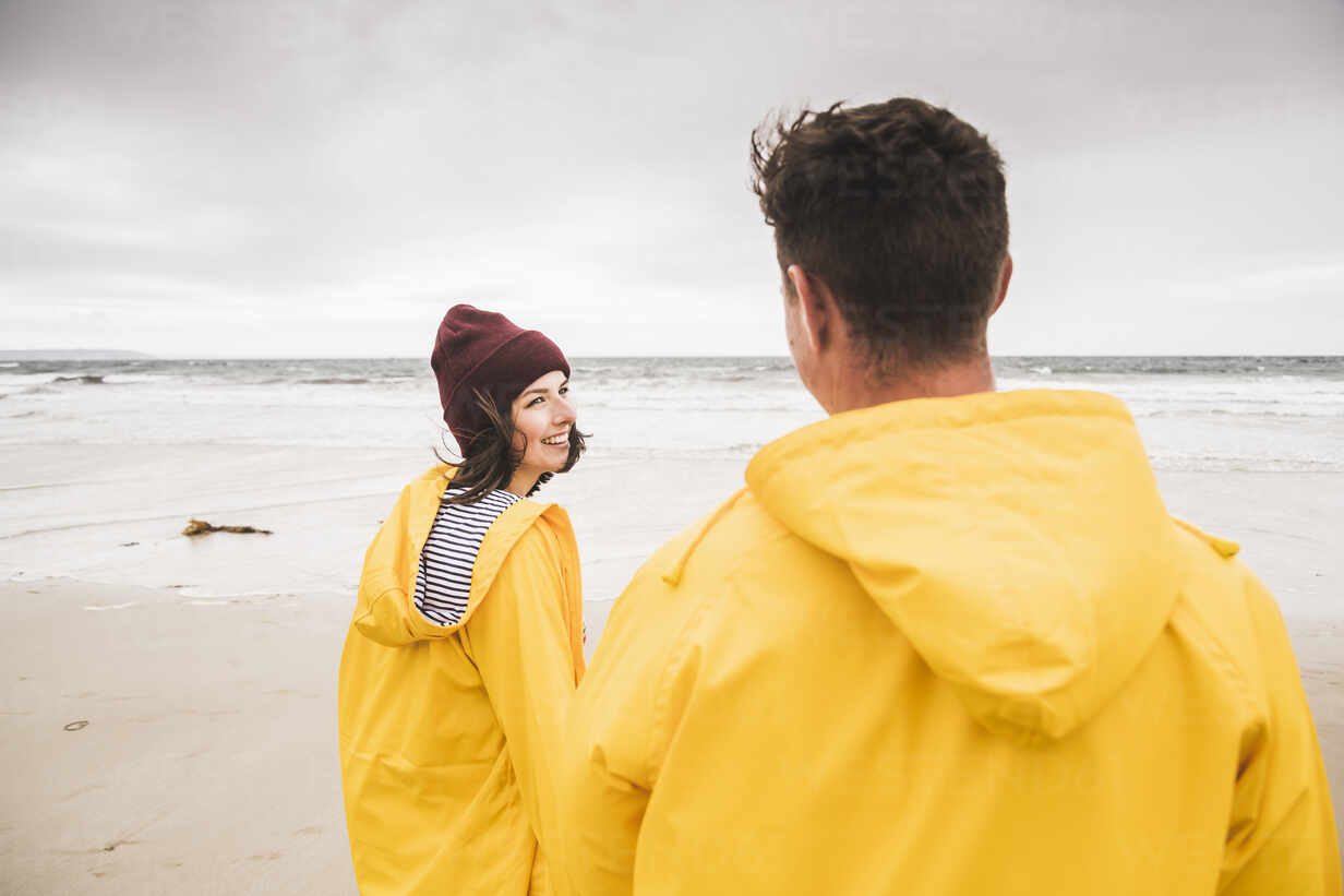 Young woman wearing yellow rain jackets and walking along the beach, Bretagne, France - UUF19689 - Uwe Umstätter/Westend61