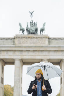 Man with umbrella using smartphone in front of Branderburg Gate, Berlin, Germany - AHSF01177