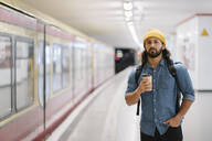 Portrait of man with backpack and coffee to go waiting at platform, Berlin, Germany - AHSF01183