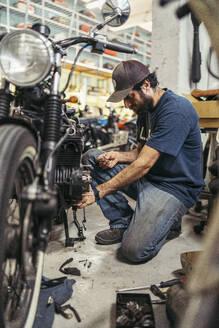 Mechanic in a repair garage repairing a motorcycle - MTBF00176