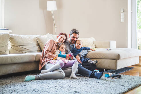 Portrait of happy parents sitting with children in living room at home - MASF14586
