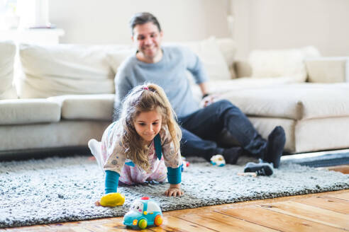 Happy man looking at daughter playing with toys at home - MASF14595