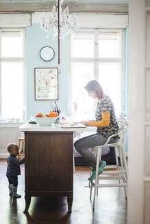 Full length of woman working on laptop with son standing by kitchen island at home - MASF14607