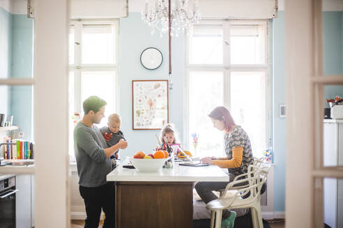 Father playing with son while standing by girl and woman busy at kitchen island - MASF14616