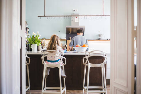 Rear view of father and daughter in kitchen at home - MASF14625