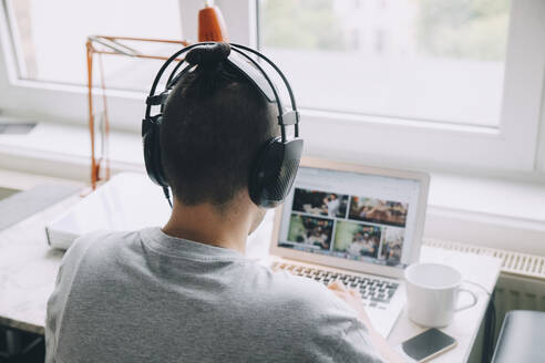 Rear view of creative businessman with headphones using laptop at desk in office - MASF14631