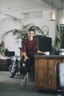 Portrait of smiling businesswoman sitting at kitchen island in creative office - MASF14685