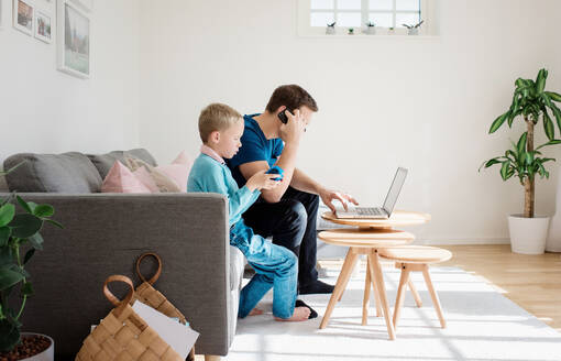 Father sat at home with his son on his mobile and laptop - CAVF69168
