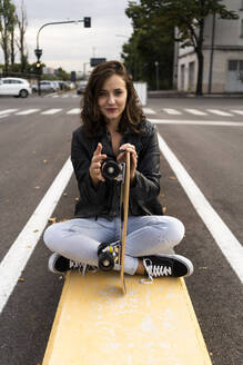 Portrait of smiling young woman with skateboard sitting on bollard - GIOF07683