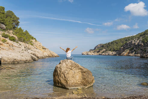 Redheaded woman with raised arms sitting on rock at the beach - AFVF04193
