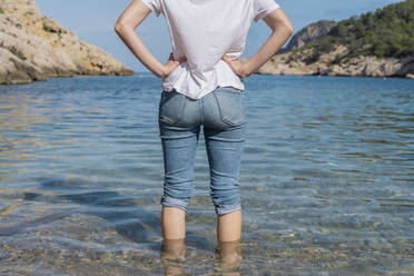 Young woman standing in water at the beach - AFVF04196