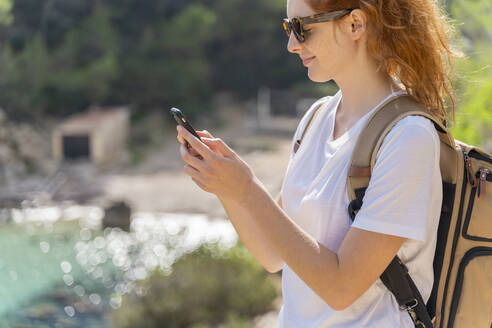 Portrait of redheaded woman using smartphone - AFVF04199