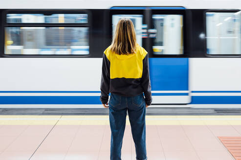 Rear view of a young woman standing on underground station platform - JCMF00276