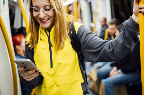 Smiling young woman standing in underground train using her smartphone - JCMF00291