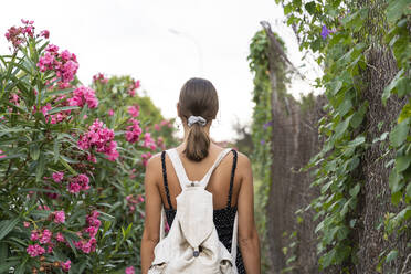 Back view of young woman with backpack strolling in a park - AFVF04203