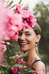 Portrait of laughing young woman in a park with pink blossoming flowers - AFVF04206