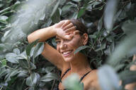 Portrait of laughing young woman among green leaves - AFVF04209