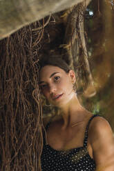 Portrait of young woman leaning against tree trunk - AFVF04212