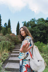 Portrait of young woman with backpack in a park raising her hand - AFVF04221
