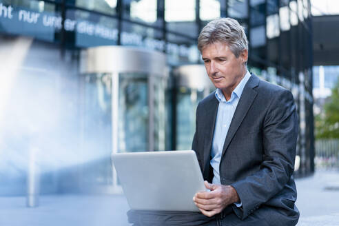 Mature businessman using laptop in the city - DIGF08886