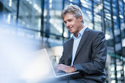 Smiling mature businessman using laptop in the city - DIGF08889