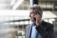 Mature businessman on the phone in the city - DIGF08898