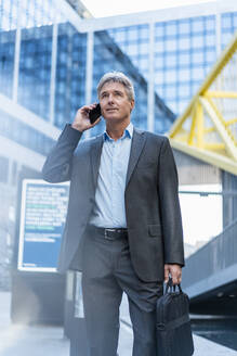 Mature businessman on the phone in the city - DIGF08901