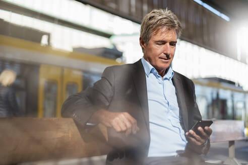Mature businessman waiting at station platform using cell phone - DIGF08907