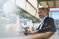 Smiling mature businessman with newspaper on station platform - DIGF08910