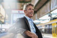 Smiling mature businessman waiting at station platform - DIGF08913