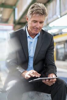 Mature businessman using tablet at station platform - DIGF08916