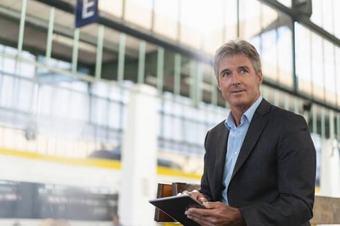 Mature businessman using tablet at station platform - DIGF08919