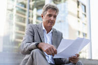 Mature businessman reviewing documents in the city - DIGF08934