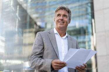 Mature businessman holding documents in the city - DIGF08937