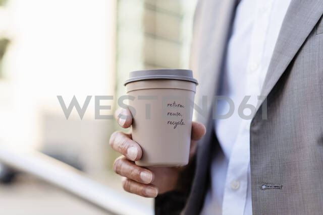 Close-up of businessman holding reusable takeaway coffee cup - DIGF08940 - Daniel Ingold/Westend61