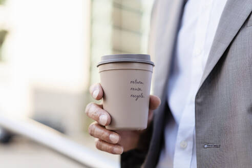 Close-up of businessman holding reusable takeaway coffee cup - DIGF08940