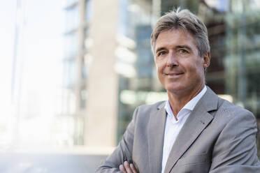 Portrait of confident mature businessman in the city - DIGF08943