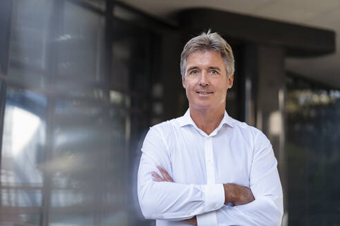 Portrait of confident mature businessman outside an office building - DIGF08946
