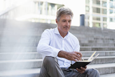 Mature businessman sitting on stairs looking at notebook - DIGF08949
