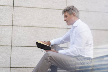 Mature businessman sitting on stairs looking at notebook - DIGF08952