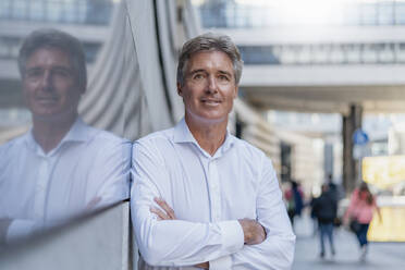 Portrait of confident mature businessman leaning against a glass front in the city - DIGF08955