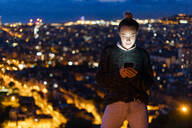 Young woman using cell phone at night above the city, Barcelona, Spain - GIOF07689