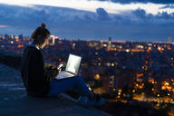 Young woman using cell phone and laptop at dawn above the city, Barcelona, Spain - GIOF07692