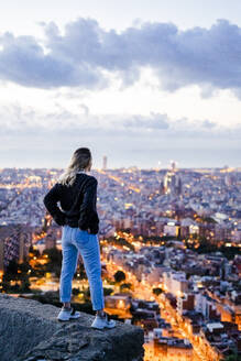 Rear view of young woman standing above the city at dawn, Barcelona, Spain - GIOF07695