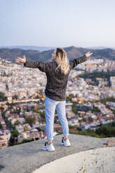 Rear view of carefree young woman standing above the city at sunrise, Barcelona, Spain - GIOF07698