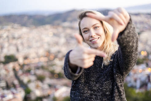 Portrait of young woman making a finger frame at sunrise above the city, Barcelona, Spain - GIOF07701
